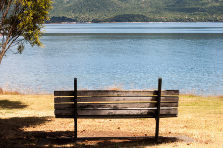 wooden bench: wooden bench next to Lake Tekapo in New Zealand Stock Photo