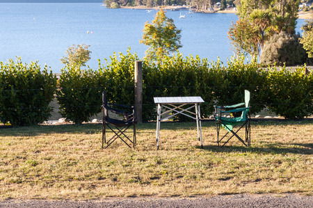 tekapo: table and chairs camping next to Lake Tekapo in New Zealand, scene of tranquility