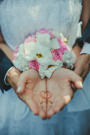 Een jong paar op hun handpalmen op de achtergrond van een bruid die een boeket van trouwringen.