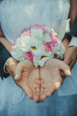 fondo elegante: Una pareja de j�venes en sus palmas de las manos en el fondo de una novia que sostiene un ramo de anillos de boda. Foto de archivo