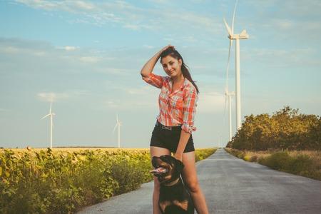 Een jong meisje, brunette met grote hond op de achtergrond van windturbines