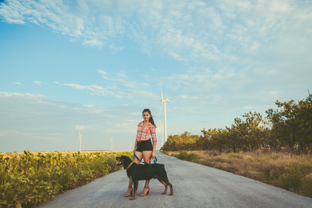 A young girl, brunette with big dog on the background of wind turbines