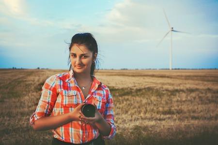 Brunette at sunset on the background of wind turbines.