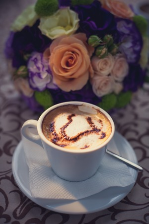 porcelain cup with coffee on the background of the bride's bouquet.