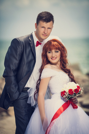 Newlyweds op plyazhe.Buket bruid met een rood lint, de bruidegom met een rode strik. Roodharige Bruid.