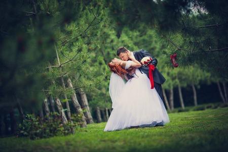 De bruidegom boog bruid kussen de borst