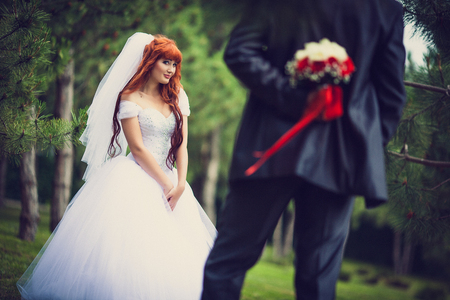 The bride is holding a bouquet behind his back