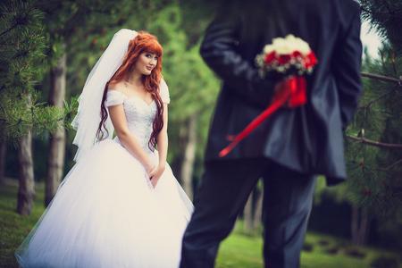 De bruid houdt een boeket achter zijn rug