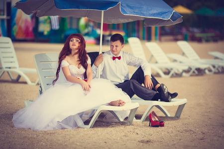 Newlyweds on the beach sitting on a deck chair. Bridal bouquet with a red ribbon, the groom with a red bow tie. Red-haired Bride. 写真素材