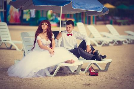 Jonggehuwden op het strand zitten op een ligstoel. Bruids boeket met een rood lint, de bruidegom met een rode strik. Roodharige Bruid.