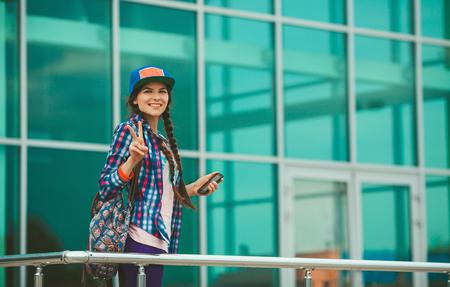Gelukkig meisje in een pet, een plaid shirt en rugzak tegen de achtergrond van grote ramen