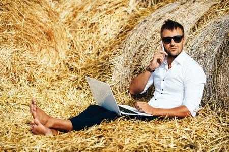Business man ziet er prachtige werken met een laptop en praten over de telefoon zit in een hooiberg. Zomervakantie in het platteland. Overal werken. Freelance op het werk. Serie.