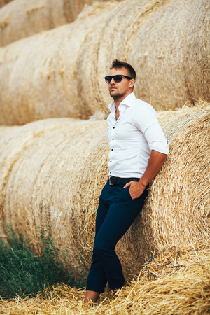 The guy in the white shirt and sunglasses posing at the straw stack. Series. 写真素材