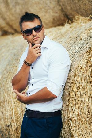 De man in het witte shirt en een zonnebril die zich voordeed op het stro stack. Serie.