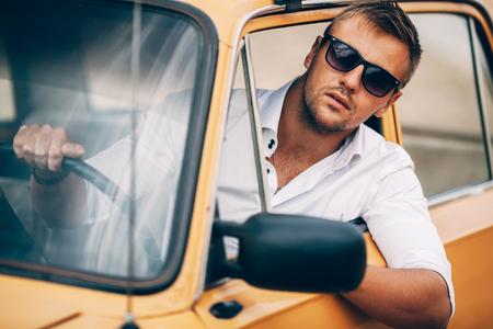 De jonge man achter het stuur van de mooie verschijning van de auto retro geel. Stockfoto