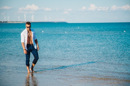 man walking on the beach. A young man in an unbuttoned white shirt on the beach. Foot-in-the water, and pants. Male athletic build. Series.