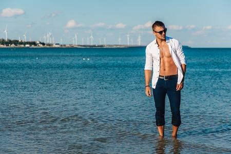 man lopen op het strand. Een jonge man in een losgeknoopt wit overhemd op het strand. Foot-in-the water, en broek. Man atletische bouw. Serie.