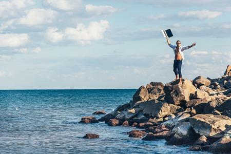 Man, zakenman, man van zaken op de zee op de rotsen in een losgeknoopt wit overhemd gelukkig hief zijn handen met een laptop. De triomf van de overwinning. Freelance.