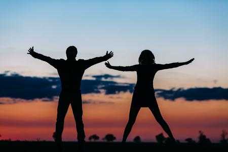 Silhouetten van de man en het meisje tegen de achtergrond van de natuur en wolken.
