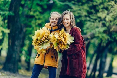 Twee zussen omhelzen, met een bos van bladeren in het park.