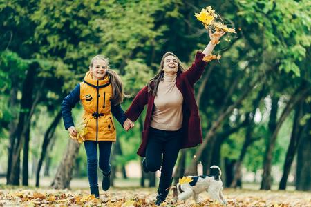 Twee zussen hand in hand tijdens het wandelen in het najaar park.