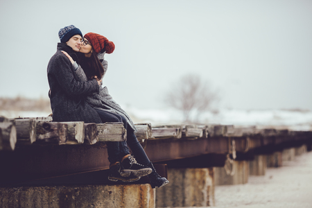 Young guy and girl in winter wear, embrace and enjoy the scenery of winter.