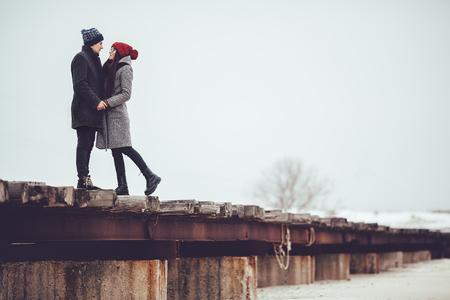 Jong jongen en meisje in de winter kleding, omarmen en genieten van het landschap van de winter. Stockfoto
