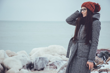 Young girl in winter sea, stones on a background of icy stares into the distance.