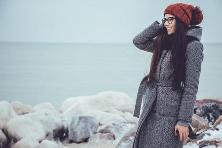 Het jonge meisje in de winteroverzees, stenen op een achtergrond van ijzig staart in de afstand.