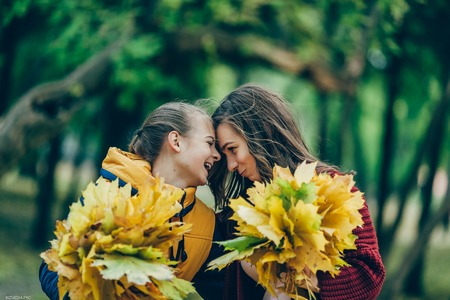 Two sisters hug, with a bunch of leaves in the park. 写真素材