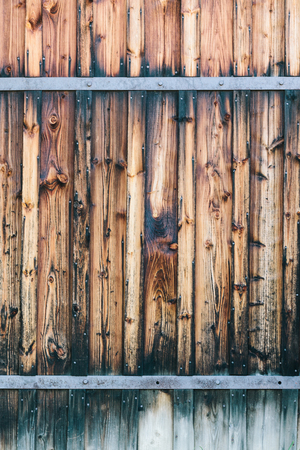 Fragment of closed wooden gate with rusty hinges