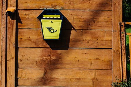 Yellow metal mailbox on a wooden wall
