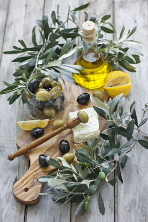 Green and black olives with bottle of olive oil on olive wood plate with traditional greek olive fork photo