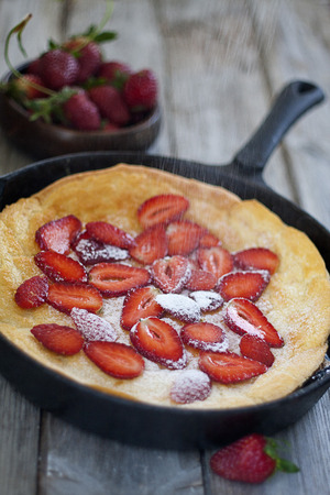 Big dutch baby pancake on pan with strawberry, dusted with powdered sugar photo