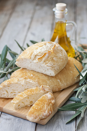 Italic traditional berad chiabatta with bottle of olibe oil and olive branch photo