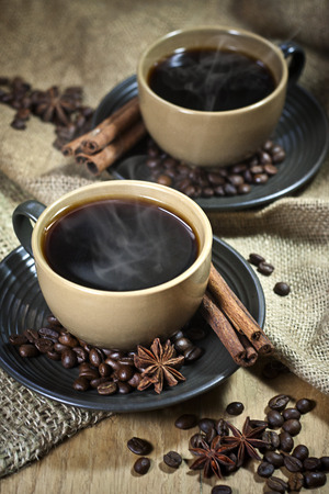 Two ceramic cups of coffee with cinamon and star anise on old coffee jute bugs photo