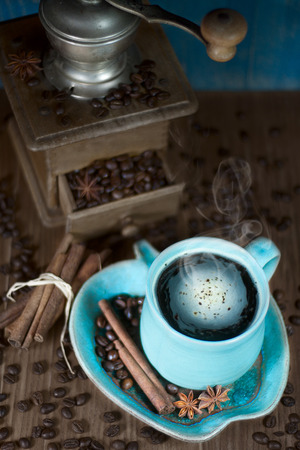 Coffee in the teal mug and old teal mill with cinnamon and star anise. Selective focus. photo