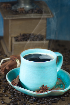 Coffee in the teal mug and old coffee mill with cinnamon and star anise. Selective focus. photo