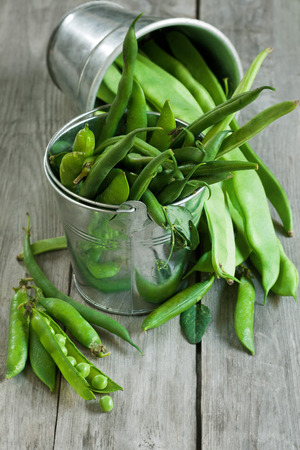 Mix green beans and peas in small buckets on old wood table. Selective focus. photo