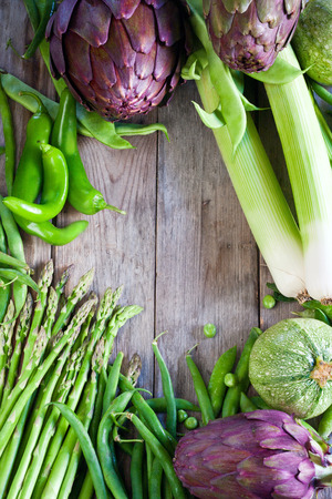 Leek, artichoke, beans, zucchini, pea on old wooden planks. Background with empty center. photo