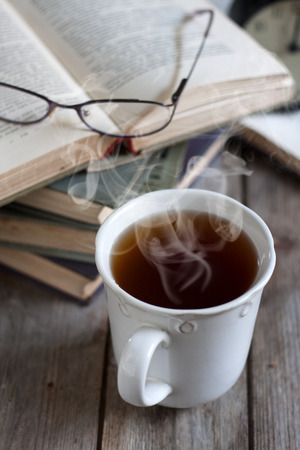 Stack of books with glasses and cup of tea. Selective focus. photo