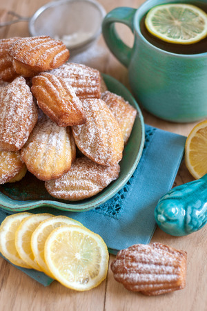 madeleine: Sugar powdered madeleines with tea and lemon. Selective focus.