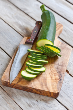 Sliced zucchini on wooden plank with knife. Selective focus.
