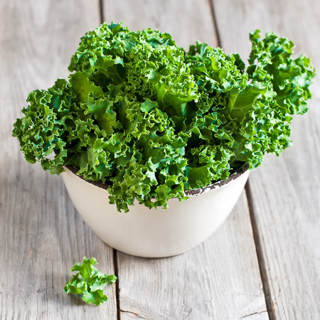 Fresh green kale in ceramic bowl. Selective focus.