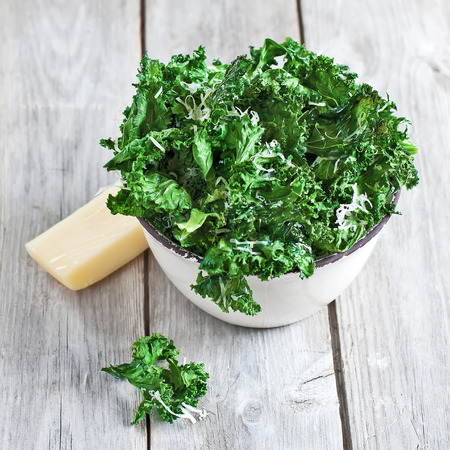 salad greens: Kale chips with parmigano cheese in ceramic bowl. Selective focus. Stock Photo