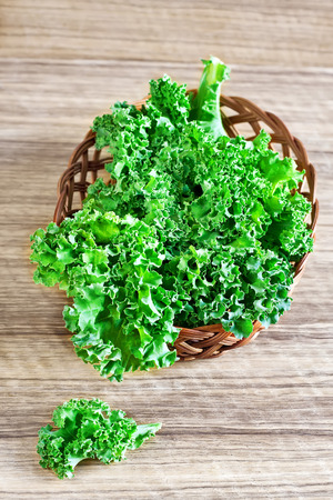 Fresh green kale leaves in basket. Selective focus. Stock Photo