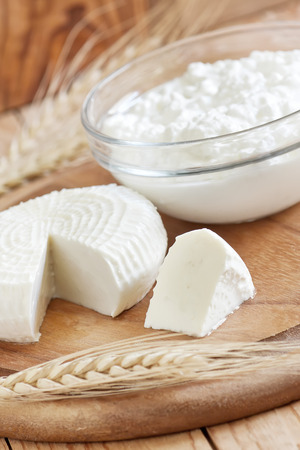 shavuot: Tzfat cheese and cottage cheese with wheat grains. Symbols of judaic holiday Shavuot. Selective focus.