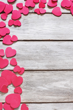messed: Copyspace old wooden background with messed red hearts.