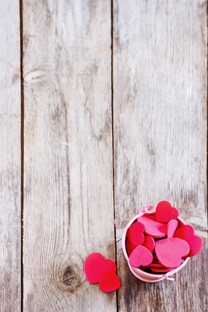 Copyspace old wooden background with small pink bucket with red hearts.
