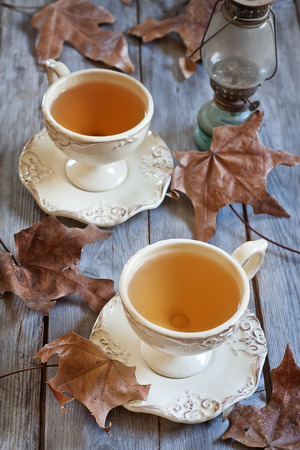 british food: Green tea in vintage mugs on wooden table with dry fall leaves. Selective focus. Stock Photo
